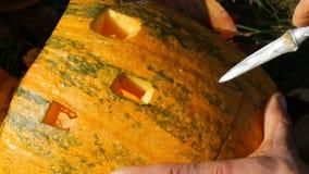 De mens snijdt gezicht voor een Halloween-pompoen Het voorbereidingen treffen voor de de herfstvakantie stock video