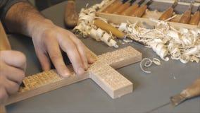 De mens snijdt houten kruis met gesneden gebeden is met de hulpmiddelen op de donkere achtergrond stock video