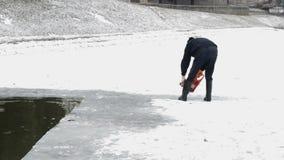 De mens snijdt Ijs met Kettingzaag op het Bevroren Meer stock video