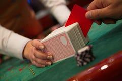 De mens snijdt kaarten met een rode kaart Stock Foto's