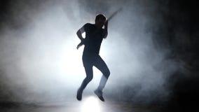 De mens speelt de basgitaar en de sprong aan de muziek stock video