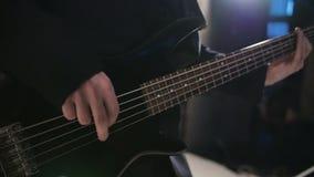 De mens speelt de gitaar Overlegpopgroep die op stadium presteert Het langzame motieinstrument spelen stock footage