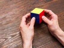 De mens speelt een kubus van Rubik op houten achtergrond royalty-vrije stock afbeelding