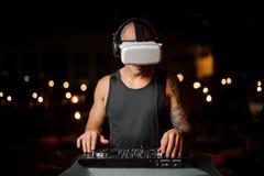 De mens speelt een mixer van DJ met virtuele werkelijkheidsglazen royalty-vrije stock foto