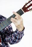 De mens speelt een snaar op de gitaar Stock Foto's