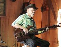 De mens speelt elektrische gitaar in een schuur tijdens een festival Stock Foto