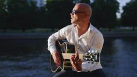 De mens speelt gitaar en zingt tegen het meer Gitarist wat betreft gitaarkoorden Middelgroot schot stock videobeelden