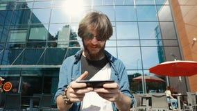 De mens speelt Spel op Telefoon stock footage