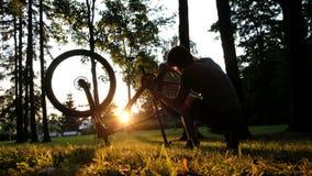 De mens spint het wiel en controleert de ketting op een omgedraaide fiets bij zonsondergang in het park stock video