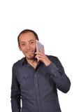 De mens spreekt bij smartphone en het glimlachen Stock Afbeeldingen