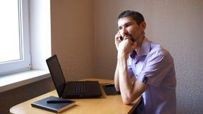De mens spreekt op telefoon dan sluit laptop en gaat weg stock videobeelden