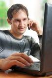 De mens spreekt telefoon en thuis het werken Royalty-vrije Stock Foto