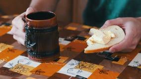 De mens spreidt boter op een brood naast een kop van hete koffie uit stock footage