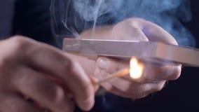 De mens steekt een gelijke met brand, vonken en rook in langzame motie, ontsteking van aan brand, open brand, hitte en vlam stock videobeelden