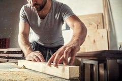 De mens steelt houten met een malenmachine stock foto