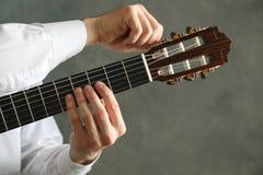 De mens stemt klassieke gitaar tegen donkere achtergrond stock fotografie