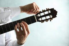 De mens stemt klassieke gitaar tegen lichte achtergrond stock afbeelding