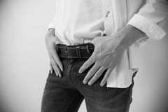 De mens stijgt zijn broek op jeanskostuum Stock Foto