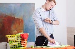 De mens strijkt kleren en bekijkt zijn horloge Royalty-vrije Stock Afbeelding