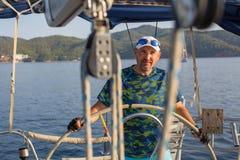 De mens stuurt de controles van een varend jacht Sport stock afbeelding
