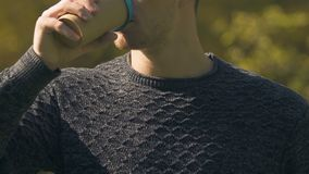 De mens in sweater het drinken koffie openlucht, ochtend begint met cafeïne, close-up stock footage