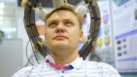 De mens telegrafeerde aan een een EEGmachine of elektro-encefalograaf die een grafisch verslag van elektroactiviteit van veroorza stock videobeelden