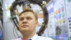 De mens telegrafeerde aan een een EEGmachine of elektro-encefalograaf die een grafisch verslag van elektroactiviteit van veroorza stock footage