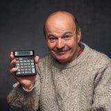 De mens telt de winsten van het inkomen op de calculator Stock Afbeeldingen