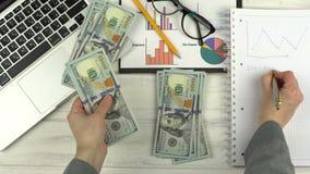De mens telt het geld en schrijft in notitieboekje stock footage