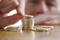 De mens telt muntstukken op een lijst Close-up van hand die een muntstuk zetten aan stapel gouden muntstukken Stock Afbeelding