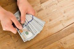 De mens telt nieuw ons dollars op houten lijst stock fotografie