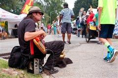 De mens tokkelt Bass Guitar For Tips At-Kunstenfestival Stock Foto's