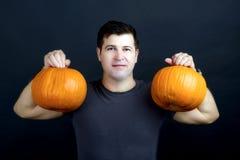 De mens toont Halloween-pompoenen Stock Afbeeldingen