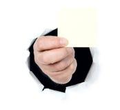 De mens toont lege kaart door een gat stock foto