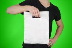 De mens toont lege plastic die zakspot omhoog op groene achtergrond wordt geïsoleerd Stock Afbeelding