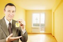 De mens toont sleutels met keychain in de vorm van een klein huis Royalty-vrije Stock Afbeelding