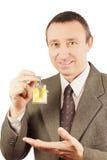 De mens toont sleutels met keychain in de vorm van een klein huis aan Stock Afbeelding