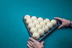 De mens treft binnen voor beginspel voorbereidingen van biljartballen met driehoek Royalty-vrije Stock Foto's