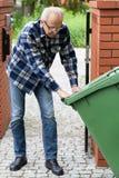 De mens trekt dumpster op wielen Stock Foto