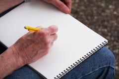 De mens trekt op sketchbook met potlood Stock Foto's