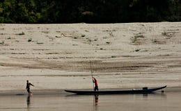 De mens trekt Vissersboot op de Mekong Rivier, Laos Royalty-vrije Stock Fotografie