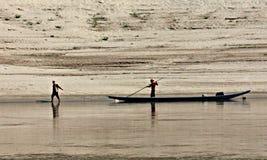 De mens trekt Vissersboot op de Mekong Rivier, Laos Stock Foto