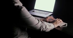 De mens typt op het toetsenbord bekijkend laptop het schermzitting bij de lijst aangaande werkplaats in dark Het proces van spijk stock footage