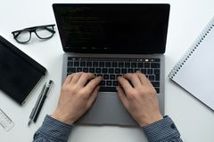 De mens typt op zijn laptop op witte lijst De hoogste vlakke mening, legt stock foto's