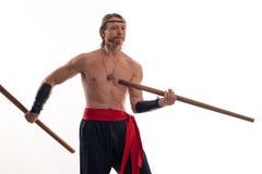 De mens van acteursAthlete in broeken met het naakte torso praktizeren met houten zwaarden Royalty-vrije Stock Fotografie