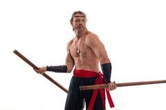 De mens van acteursAthlete in broeken met het naakte torso praktizeren met houten zwaarden Royalty-vrije Stock Foto
