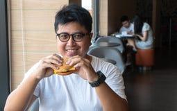 De mens van Azië eet hamburger in een snel voedselrestaurant en geniet van heerlijk voedsel mens die in een Witte t-shirt en glaz stock afbeelding