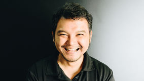 De mens van Azië het lachen glimlach in donkere stijl Stock Foto