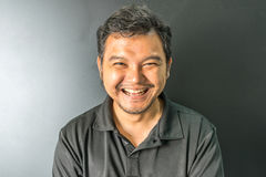 De mens van Azië het lachen glimlach in donkere stijl Stock Fotografie