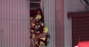 De mens van brandbestrijdersreddingen in het voortbouwen op brand wordt opgesloten die stock videobeelden